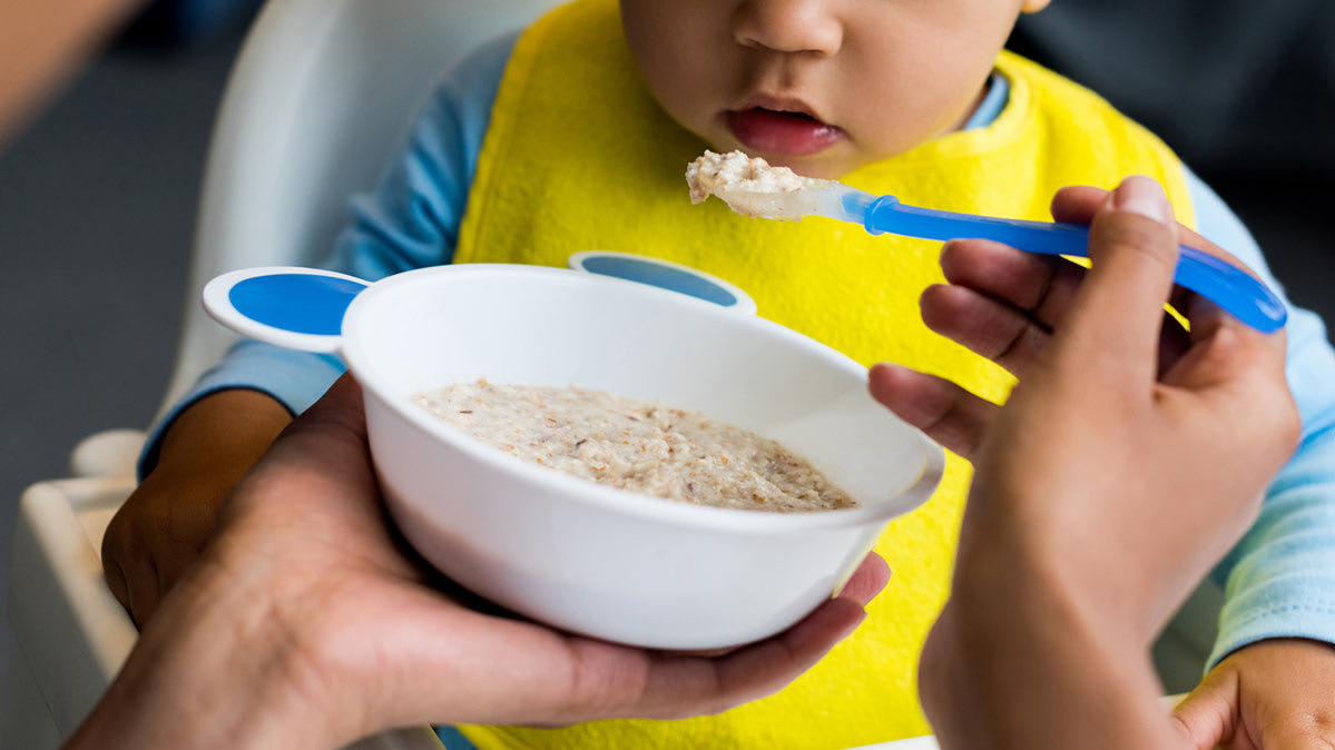A child being fed baby food from a bowl with a spoon