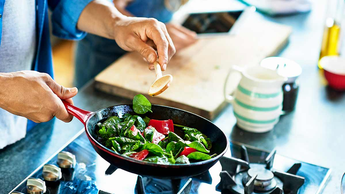 Stir-frying spinach and other vegetables as part of an anti-inflammatory diet.