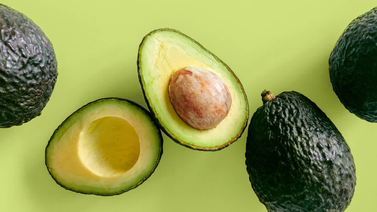 Several Hass avocados, including one cut in half with the pit showing