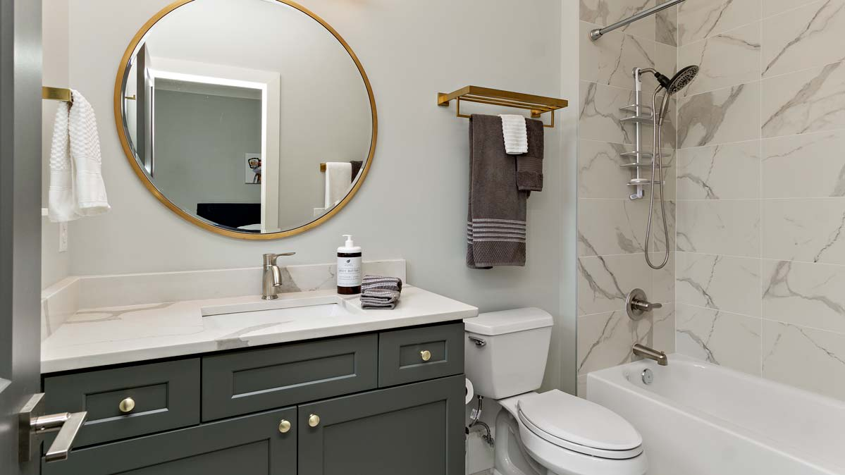 A modern example of how to organize a small bathroom with toilet paper holders and a metal caddy.