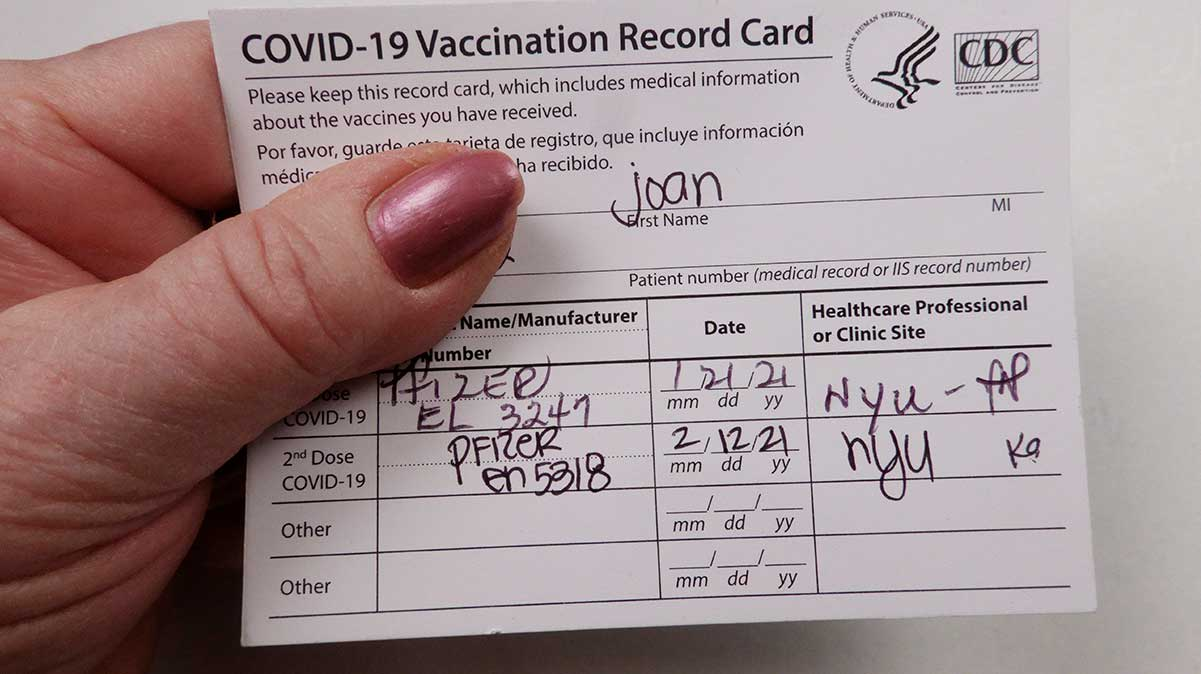 A person holding a COVID-19 Vaccination Record Card