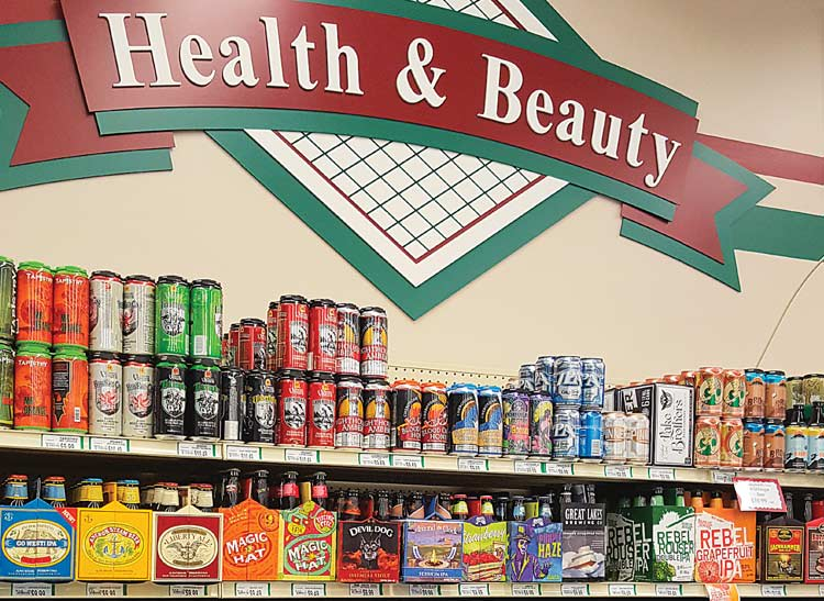 A photo of a grocery store shelf stocked with beer under the a sign marked for health and beauty products.