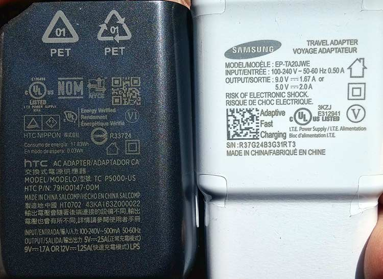 Closeup of a smartphone charging adapters from HTC (left) and Samsung (right), each adorned with more than a dozen certification symbols