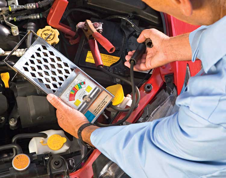A person from CR's labs running a diagnostic test on a car battery.