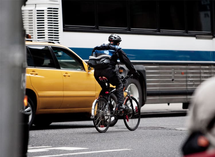 Bicylist rides in traffic to the right of a taxi and bus.