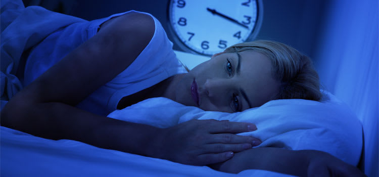 A woman lies awake considering whether to take suvorexant