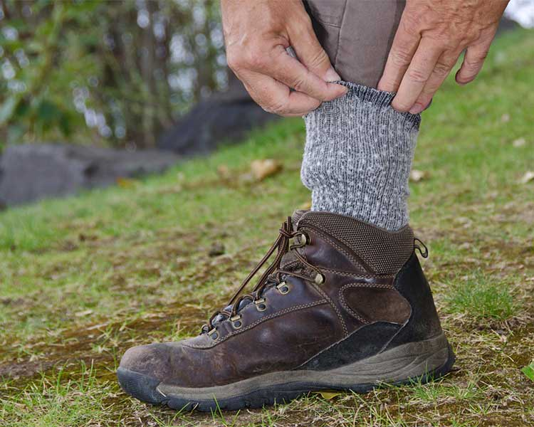 A man tucking pants into his socks to avoid ticks.