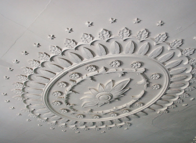 Plaster ceiling medallion painted with white paint.