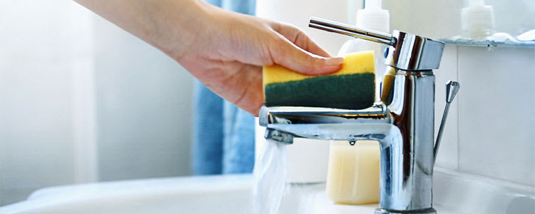 Someone cleaning a sink with homemade cleaning supplies.