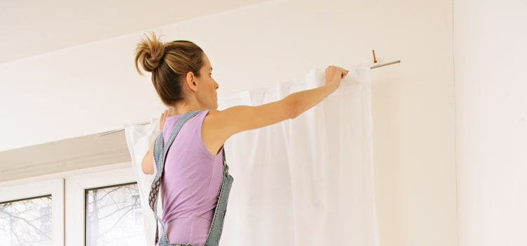 A woman on a ladder preparing to clean curtains.