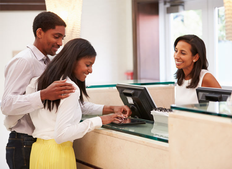 A couple checks into a hotel using one of their rewards cards