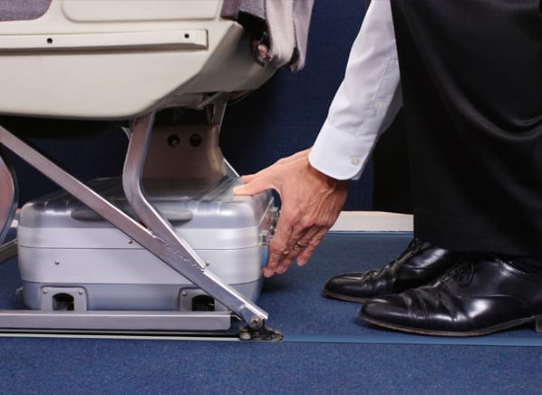 Photo of a man storing a personal item under the seat in front of him.