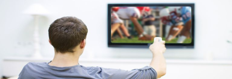 Photo of someone using a remote cotrol and watching a football game on a best TV.