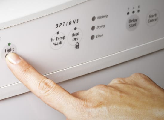 A person pushing the heated dry button on a dishwasher control panel.
