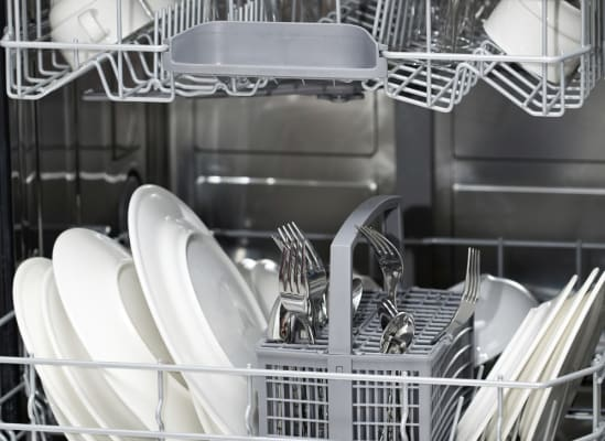 The inside of a dishwasher, loaded with dishes, to show its stainless steel tub.