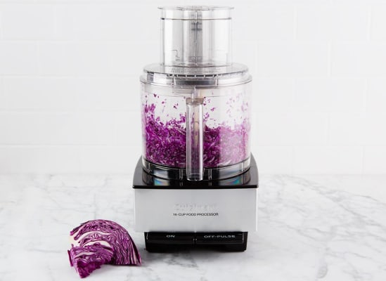 Photo of a food processor shredding red cabbage.