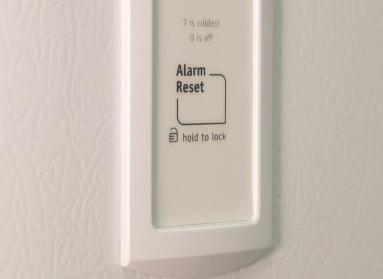 An alarm reset button on a freezer.