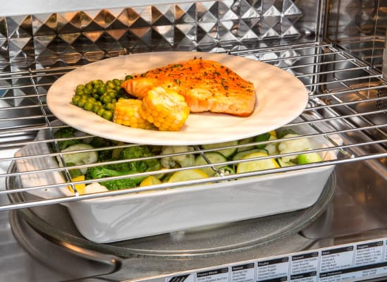 Two microwave racks, being used to warm vegetables on the bottom and reheat salmon on the top.