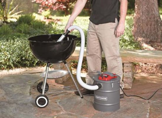 A person using a wet/dry vacuum to clean ashes out of a patio grill.
