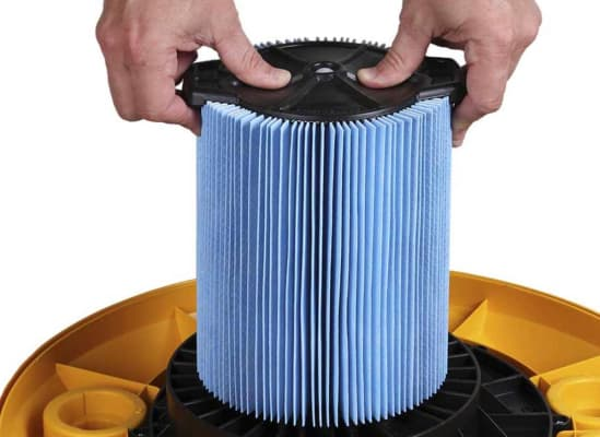 A person putting a new, clean filter into a wet/dry vacuum.