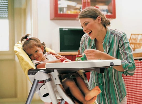 Photo of a child sitting in a high chair that has seat-adjustment options.