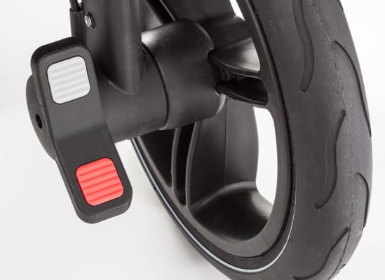 A foot-activated brake/parking pedal on a stroller.