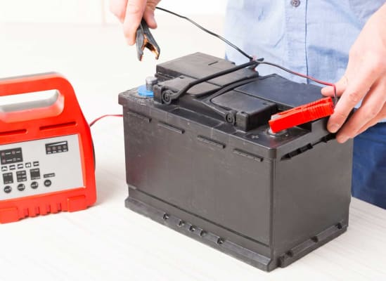 A person attaching a float charger to a car battery.