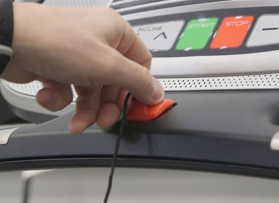A person holding a treadmill's tether safety keyl.