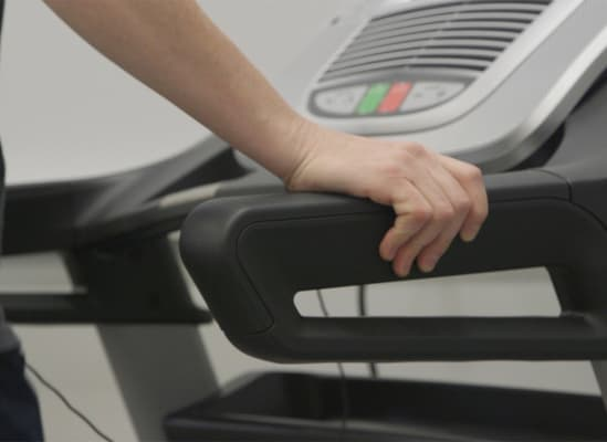 A person using the handrails on a treadmill.