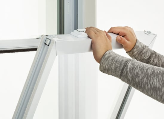 A person installing tilt-in sashes.