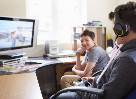 Photo of two kids playing a video game on a computer.