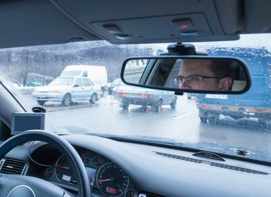 A man driving in traffic while it's raining.