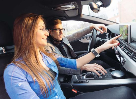 A woman looking at the screen of a dash-mounted GPS while riding as a passenger in a car.