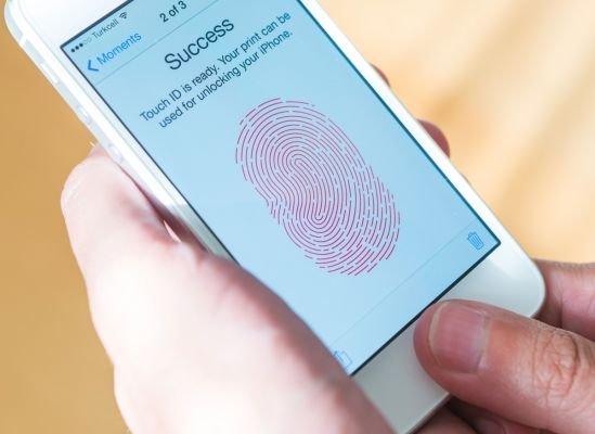 Picture of someone using a thumbprint to unlock a phone.