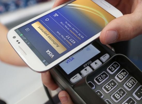 Someone using NFC (near field communication) by waving a smartphone at a store register to pay.