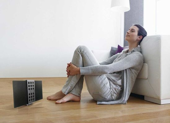 Photo of a woman listening to a BenQ treVolo wireless speaker.