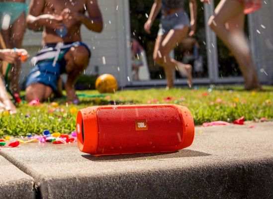 Photo of a JBL Charge 2 wireless speaker being used outside at a pool party.