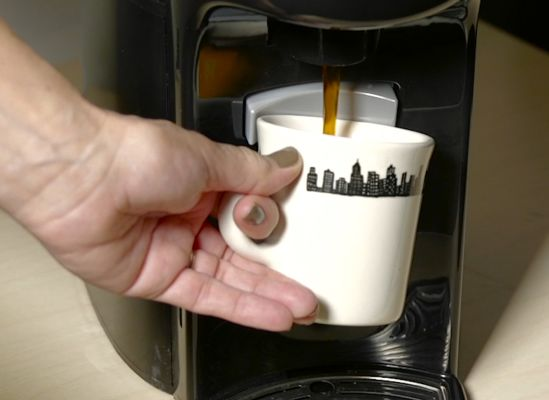 Person serving themselves a cup from a self-serve machine.
