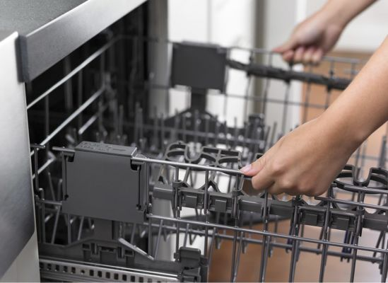 A person adjusting the extra rack on a dishwasher.