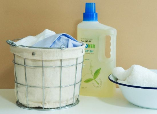 Photo of a wire basket of laundry, a bowl and towel, plus a container of