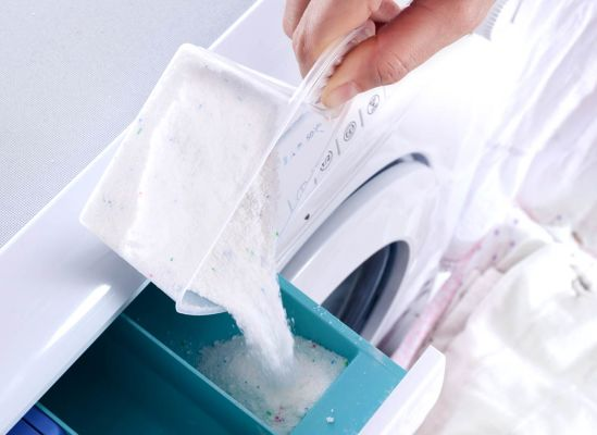 Photo of a person pouring powdered detergent into a washing machine.