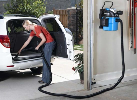 A woman cleaning her car using a wet/dry vacuum that's mounted on the garage wall.