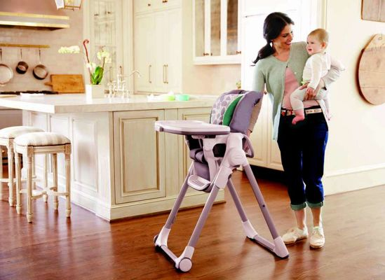 Photo of a mom holding her baby and standing next to a foldable high chair.