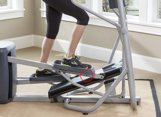 Photo of a person using elliptical trainer highlighting safety pin to prevent pedaling.