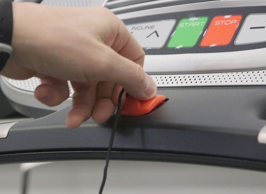 A persn holding the tether safety key on a treadmill.