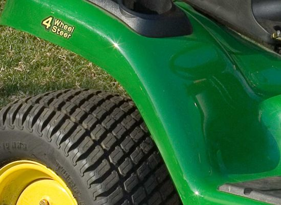 A four-wheel steering sticker on a lawn tractor alerting users that the model can make tight turns.
