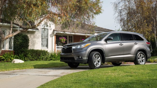 grey 2015 Toyota Highlander in driveway in front of a house