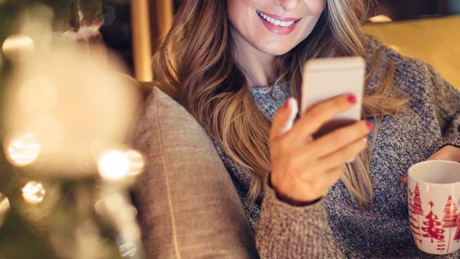 Woman on smart phone in front of christmas tree