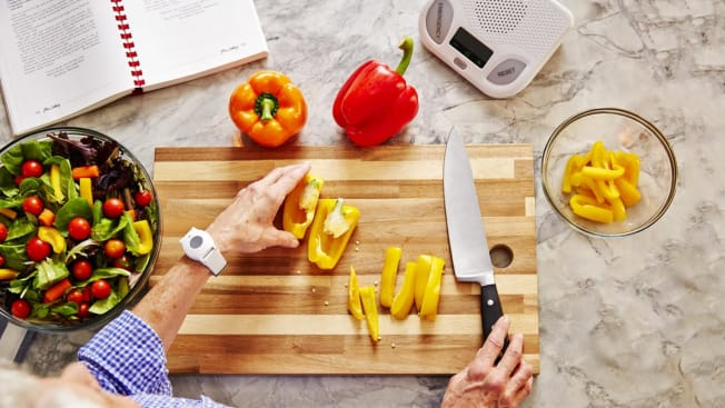Woman in kitchen cutting peppers for salad wearing life alert device