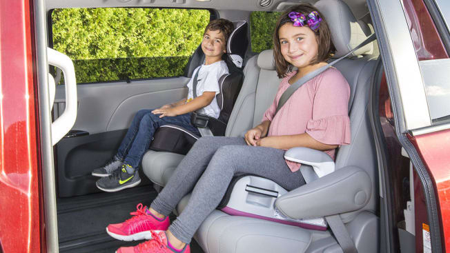 Children sitting in booster seats in a minivan.